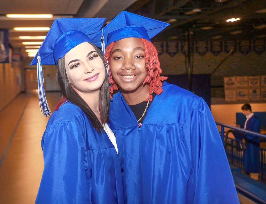 JULIA GUTHRIE, left, and Jadyn Chestnutt meet in the gymnasium with fellow graduates before the ceremony begins.