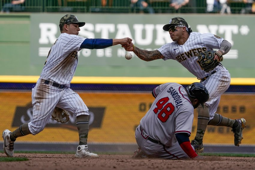 MILWAUKEE BREWERS' Kolten Wong and Luis Urias fumble the ball as Atlanta Braves' Pablo Sandoval slides safely into second during the seventh inning Sunday's game, in Milwaukee.
