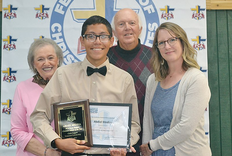 ABDIEL MEDINA of Cleveland High School was named FCA Athlete of the Year, and was awarded the Chris Leggett Memorial Scholarship. From left are: Linda Leggett, Chris Leggett's grandmother; Medina; Jay Leggett Sr., Chris Leggett's grandfather; and Jackie Leggett Stanley, Chris Leggett's widow.