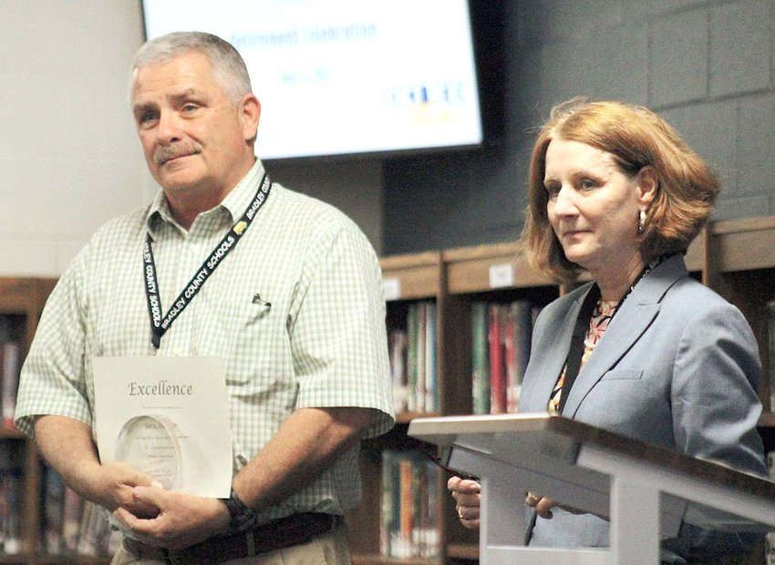 RETIRING STAFF member Gary Austin, transportation director and former teacher, holds a certificate and keepsake from Bradley County Schools as his colleagues say kind words about his service to the school system. To his right is Director of Schools Dr. Linda Cash.