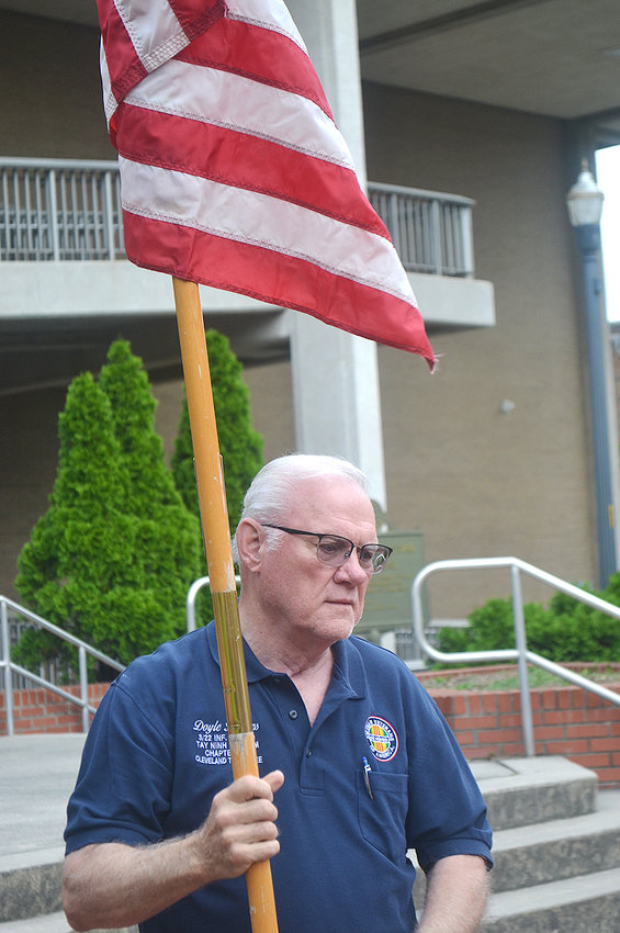VIETNAM WAR VETERAN Doyle Hughes holds one of the flags that was set up at the Bradley County Courthouse Friday morning in anticipation of the Memorial Day ceremony to be held there on Monday.