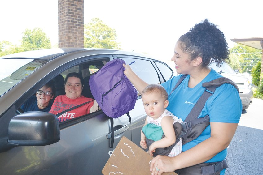 PEERLESS ROAD CHURCH volunteer Linda Randolph, with Annahlyse, hands a backpack to Amanda Forgey at Wednesday's giveaway at the church.