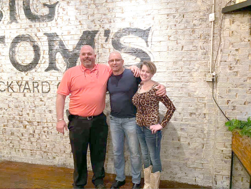 """BIG TOM Anderson, left, who owns Big Tom's Backyard Grill & Bar with his wife, Sabrina, right, pose with Robert Irvine, center, host of the Food Network's """"Restaurant Impossible."""" The eatery was featured on the television program earlier this year."""