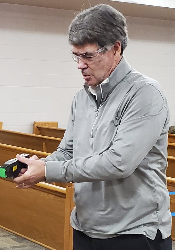BRADLEY COUNTY Commissioner Bill Winters, a member of the Law Enforcement Committee, prepared to fire a Taser during a demonstration of the equipment.