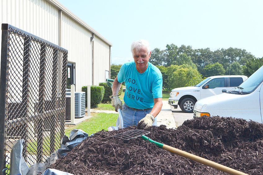 MARK SNOWDEN gets a shovel full of mulch that he placed around shrubs at the Bradley/Cleveland Senior Center Sunday.