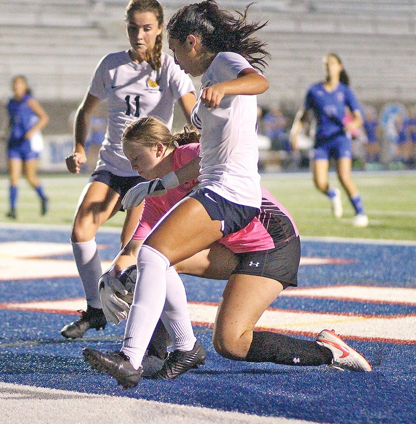 """CLEVELAND FRESHMAN goalkeeper Reagan McKinley, center, snatches the ball away from a scoring attempt by Walker Valley junior Brianna Romero (10), with senior teammate Sydney Ellis (11)   closing in during Tuesday evening's District 5-AAA battle at """"The Benny."""" McKinley had 13 saves in the stunning 2-0 Lady Raider shutout victory."""