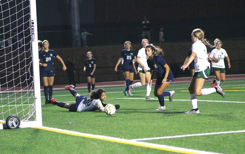 WALKER VALLEY senior goal keeper Isabella Blair deflects a Rhea County shot to prevent a goal, while teammate Nanhi Medrano (22) closes in during Thursday  evening's 2-1 victory over the Lady Eagles, at Lee University's Ray Conn Sports Complex.
