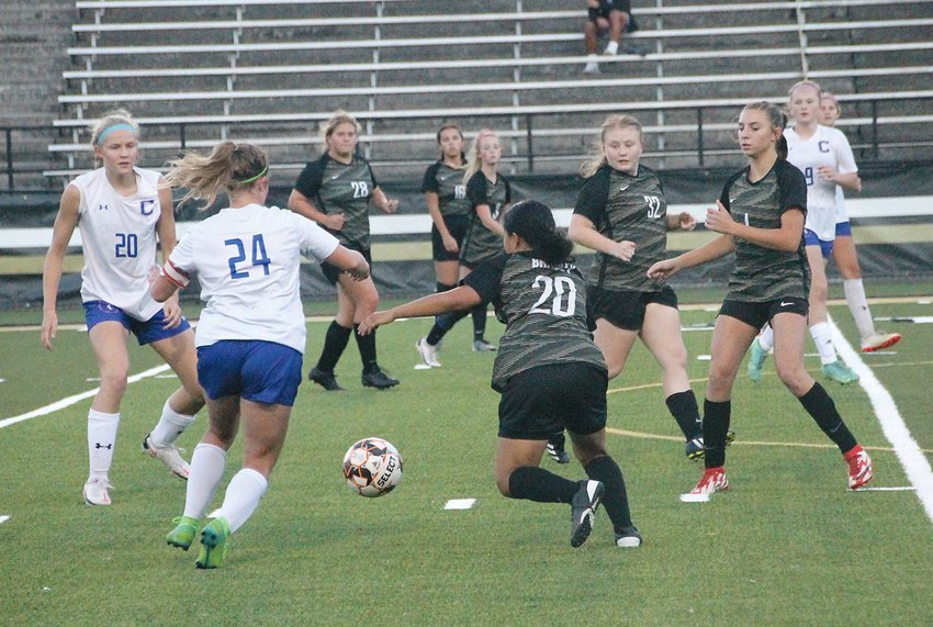 CLEVELAND HIGH senior Grace Longley (24) and Bradley Central's Susan Ashbie (20) battle for the ball while teammates close in during Thursday evening's District 5-AAA battle, at Bear Stadium. Longley later scored the match's only goal.