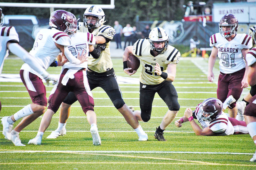 BRADLEY CENTRAL sophomore Jackson Wilson (22) follows the block of teammate Luke Keith (65) through an open hole for some of his 220 yards in Friday's 28-16 Region 2-6A win over Bearden, at Bear Stadium.