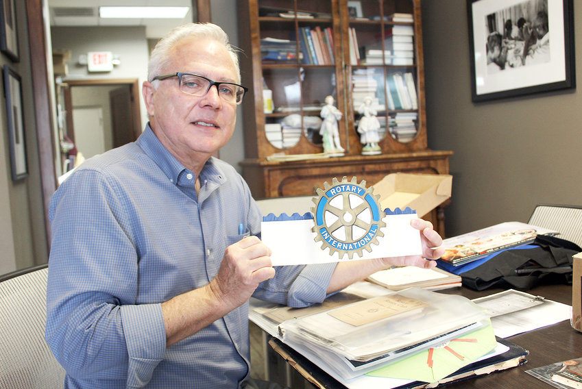 ROTARY Club of Cleveland member David Carroll holds a commemorative hat used during the club's 25th Anniversary celebration in 1949. The club is gearing up for its Centennial.  Many items in the collection were donated by the Fillauer family.