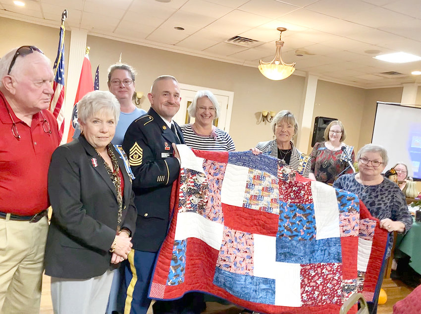 Kathay Pegram with Quilts of Valor presented a quilt to Command Sergeant Major Richard Blair at the October meeting of Ocoee Chapter, NSDAR. CSM Blair entered active-duty service in 1988 where he has served in various positions. CSM Blair holds a bachelor's of science degree in industrial technology from Tennessee Technological University and is currently employed as a recover boiler operator with Resolute Forest Products. His awards and decorations include Meritorious Service Medal, Army Commendation Medal with one silver oak leaf cluster, Army Achievement Medal with one bronze oak leaf cluster, National Defense Service Medal and many more. Joanne Swafford, Ocoee Chapter First Vice Regent, pieced the top of the quilt and Beth Spencer quilted the blanket. In attendance were the parents of CSM Richard Blair, B. R. and Mary Charles Blair. Also attending was CSM Richard Blair's wife, Michelle Blair. The mission of the Quilts of Valor Foundation is to cover Service Members and Veterans touched by war with comforting and healing Quilts of Valor. From left are B. R. Blair, Mary Charles Blair, Michelle Blair, CSM Richard Blair, Beth Spencer, Joanne Swafford, Leigh Ann Boyd, and Kathay Pegram.