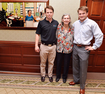 Will Jones, left, and Bailey Jones pose with Margaret Duggan at Check Into Cash's 20th anniversary celebration in 2013.
