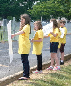 STUDENTS from Park View Elementary School wave to motorists heading to Bradley Central High School while participating in the Happiness Sprinkling Project at the end of a recent school day.