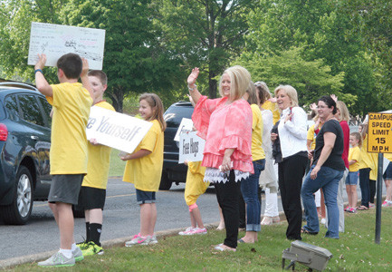 SMILES, WAVES AND KIND WORDS are shared with passing motorists as Park View Elementary students, parents and Bradley County Schools administrators take part in the Happiness Sprinkling Project.