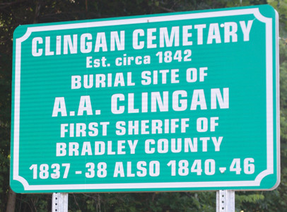 A road sign marking the location of the cemetery on the east side of the roadway near Cleveland Middle School.