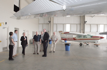 MONTGOMERY AERO ENTERPRISE personel stand with Cleveland Muncipal Airport Authority members and jetport staff in the maintenance hangar during a tour.