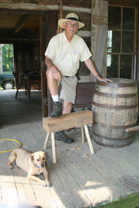 Tom Newman, seen with his dog, Hazel, has five restored cabins on his property.