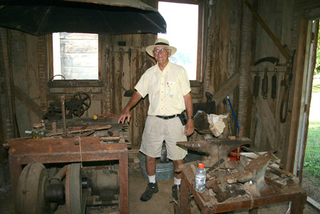 THIS BLACKSMITH SHOP with authentic anvils is where blacksmiths worked to make horseshoes and other tools for use in the 1800s. Tom Newman admits he made some of the tools hanging in this shop, but others were made by blacksmiths of the 17th century.