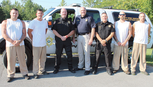 Sheriff Eric Watson, center, poses with officers and inmates involved with the BCSO's litter pick-up detail. From left are inmates Justin Davis and Michael Johnson, Deputy Mack Beasley, Watson, BCSO Environmental Officer Tim Mason, and inmates Scott Millsaps and James Holder.