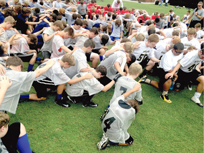 MIDDLE SCHOOL football players pray for each other during a summer camp hosted by Fellowship of Christian Athletes of the Ocoee Region at Lake Forest Middle School. Students are encouraged to live lives of faith while excelling in their sports.