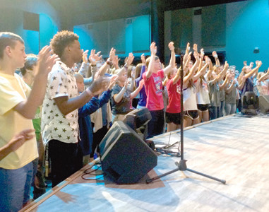 STUDENT LEADERS participate in a Christian worship service during a leadership event for youth who serve as Fellowship of Christian Athletes leaders at their schools. The optional extracurricular program offered at local schools combines faith and athletics.