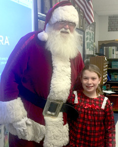 MAEVE CLARK, a fourth-grader at Hopewell Elementary School, meets Santa Claus during recent Christmas-themed festivities at the school.