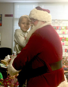 MASON LOMBARDI, a first-grader at Hopewell Elementary School, spends some time with Santa Claus during recent festivities at the school.