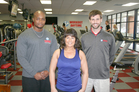 MANY PEOPLE want to be able to work out anytime, when considering fitness center activities. Above, Dennis Greene, left, and Lisa Bandy, posed with Ryan Strother, the owner and operator of the Workout Anytime fitness center in Cleveland. The 24/7 workout schedule is a huge plus for the facility, according to Strother. It seems more and more people in Cleveland are taking their health seriously and developing an exercise routine.