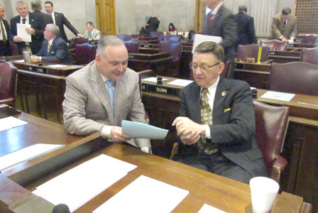 State Reps. Kevin Brooks and Dan Howell discuss a bill while on the floor of the state House of Representatives.