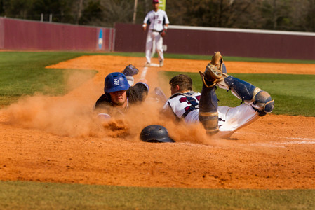 LEE UNIVERSITY senior catcher Nate Wierzgac (35) dives to make a tag at the plate as a Shorter University base runner tries to score during the first game of Saturday's Gulf South Conference doubleheader at Olympic Field. The Hawks won the opener 3-2 in 12 innings, but the Flames came back for an 8-1 win in the nightcap. The teams play again this afternoon at 1.