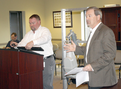 ELECTRIc DIVISION manager Bart Borden, right, and electrical engineer Jeff Luther, left, discussed some new equipment with the utility's board. The item sitting between the two presenters is a trip saver single-phase recloser.