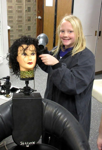 ARIANNA CARVER of Waterville Community Elementary School styles a mannequin's hair in a cosmetology class at Bradley Central High School.