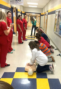 FIFTH-GRADERS learn how to perform CPR on dummies, under the instruction of Walker Valley High School health science students.