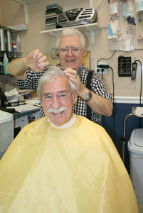 WATSON HORNE turned 80 recently. Horne is seen cutting the hair of one of his loyal customers, Earl Rowan, a retired teacher from Bradley Central High School who had a 50-year career in education. Rowan has been a regular customer of Horne since 1965.