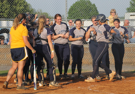 "WALKER VALLEY senior Ali King (with helmet) is greeted at home plate by ""Feisty Fillies"" teammates and assistant coach April Richards, far left, after blasting a two-run homer in Wednesday evening's District 5-AAA victory over Bradley Central at Bob McKenzie Field."