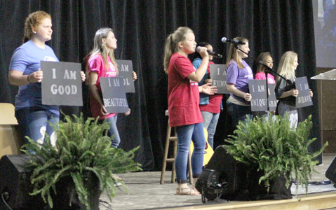 "RAYLEIGH HAWKINS, center, is joined by fellow Boys & Girls Club members on stage while singing at Thursday's ""Empowering Women"" event at Omega Center International."