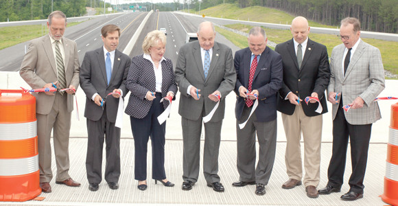 U.S. AND STATE political leaders join Mayor Tom Rowland and his wife, Sandra, in the ribbon cutting ceremony at the dedication. Pictured from left are Mayor D. Gary Davis, U.S. Rep. Chuck Fleischmann, Sandra Rowland, Mayor Tom Rowland, State Rep. Kevin Brooks, U.S. Rep. Scott DesJarlais and Tennessee Department of Transportation Commmissioner John Schroer.