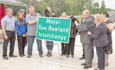 MAYOR TOM ROWLAND, along with his wife Sandra and members of his family, unveil the Mayor Tom Rowland Interchange sign at the dedication on Friday on APD 40.