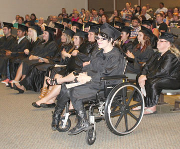 DANIELLE GIBBY, center, grins while participating in Thursday's Adult Education commencement for  Bradley and Polk counties, held at Cleveland State Community College. She was one of 23 local adults who chose to take part in the festivities after earning high school equivalency diplomas.