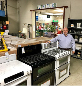CHIP WILLIS, executive director of Habitat for Humanity of Cleveland, shows off some of the Whirlpool ranges on display on the sales floor of one of two Habitat ReStore centers located in Cleveland. Not only does Whirlpool furnish Habitat homes with appliances, it also makes appliance donations to ReStores. Most recently, Whirlpool announced the funding of $90,000 for a new Habitat home in the Blythe Oldfield neighborhood, which is not far from the site of the former Whirlpool manufacturing complex.