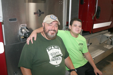 JAMIE LEWIS poses with his son Brody at the West Polk County Fire and Rescue Department in Benton. Brody, 12, is already on track to join the Boy Scouts Explorer Program, which provides students with an opportunity to learn about a variety of career fields. Lewis has been serving in the U.S. Coast Guard Auxiliary since 1998, and recently started to work as field services coordinator for Meridian Wildlife Removal Services. He said he is a very proud parent.