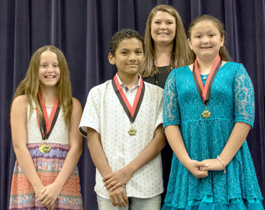 WRITING AWARDS were given to students, from left, Mikaela Burger, Isaiah Calderone and Sky Emerton at Stuart Elementary School. Presenting them is teacher Kristin Gowin.