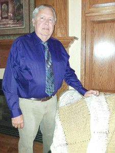STEVE ELLIOTT STANDS with the blanket he received in the mail from former student Kara Jo Brigham.