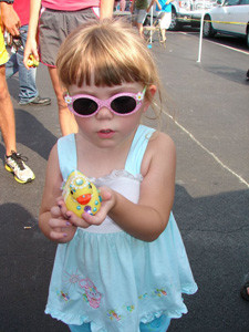 A youngster shows off her duck, all dressed up and ready to run a Great Cleveland Duck Race from the past.
