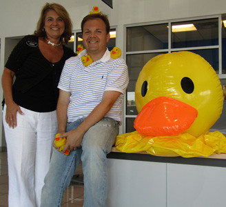 "Debbie Melton of Don Ledford Automotive Center gets ""ducky"" with Mix 104.1's Steve Hartline, in preparation for Friday's annual Duck Race, which will also serve as the official celebration for the station's 60th anniversary."