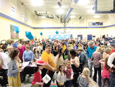 CROWDS mingle during Michigan Avenue Elementary School's annual community auction. It is the school PTO's largest event each year.