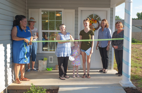 SHEILA BELL and her family prepare to cut the ribbon signifying the beginning of their lives as homeowners.  From left are Habitat for Humanity representative,Nacole Harris Massengill, Bell family advocate Fran Henry, Sheila Bell, Jazmine Bell, Amy Bell, Brandi King and Shannon Ingram.