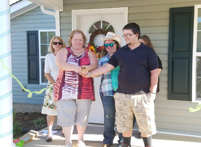MELISSA STAFFORD and her family, daughter, Haley, and son, Austin, cut the ribbon to their brand new home at the Habitat for Humanity of Cleveland home dedication celebration.