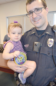 15-MONTH-OLD Isabella Humberd was happy to receive a CPD patch at the Police Youth Academy graduation Friday. Holding the infant is Geoffrey Humberd.