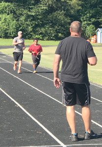 LEAF ACADEMY instructor Robby Hair runs track with one of the cadets in the academy. The group of 20 participants in the academy graduated Friday during ceremonies at Cleveland Middle School.